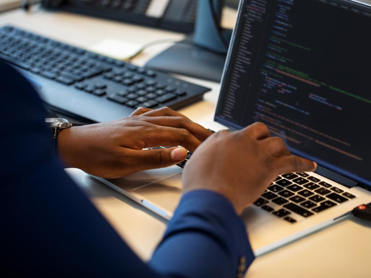 black computer programmer hands over a laptop